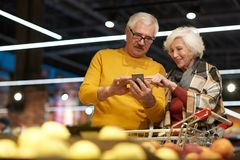 Seniors Using Smartphone in Supermarket. Portrait of cheerful senior couple grocery shopping in supermarket, using smartphone to read shopping list and calculate Royalty Free Stock Images