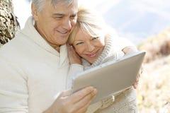 Seniors using tablet outdoors royalty free stock photo