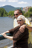 Seniors on Vacation. A handsome senior couple take in the sights at a lakeside resort in Magog, Quebec while on vacation. The peak in the background is Mont stock images
