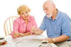 Seniors Voting from Home. Senior couple filling out their absentee ballots at home. Isolated on white stock image