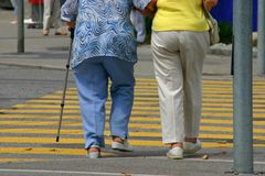 Seniors walking. Two grandmas, one with walking aid,  about to cross pedestrian lane. Fitted for seniors fitness, rehabilitation, spa programs for elderly Royalty Free Stock Photography