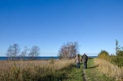 Seniors walks along coast Stock Photos