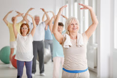 Seniors during warm-up. Group of happy seniors during warm-up before exercise Royalty Free Stock Photo
