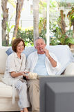 Seniors watching tv at home. And eating Stock Images