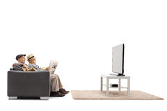 Seniors watching tv and reading a newspaper Royalty Free Stock Photo