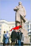 Seniors wiht reg flag speaking to each other under Lenin monumen Stock Image