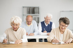 Seniors writing test. Group of seniors writing an IT test in white classroom Stock Images