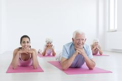 Seniors and yoga instructor. Group of seniors and young yoga instructor cooling down after exercising stock photos