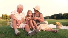 Seniory i wnuczka używa komputer osobisty pastylkę outdoors zdjęcie wideo
