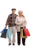 Seniory patrzeje ono uśmiecha się i kamerę z torba na zakupy Obrazy Royalty Free