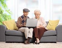 Seniory siedzi na kanapie i używa laptop Obraz Stock
