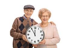 Seniory trzyma ściennego zegar Zdjęcie Royalty Free
