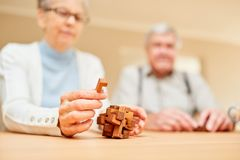 Seniory z demencją bawić się z drewnianą łamigłówką obraz royalty free