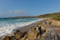 Sennon-Buchtstrand Cornwall mit den Leuten, welche die blauen See- und Weißwellen genießen lizenzfreie stockbilder
