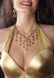 Seno della donna in costume dell'oro con monili Fotografia Stock