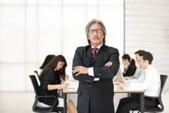Senoir businessman standing while other junior businessmen sitting in background in modern office royalty free stock images