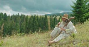 Senoir podróżnik w starych ubraniach wącha kwiaty podczas gdy siedzący na trawie w górach Horyzontalny widok zbiory wideo