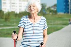 Senor moderno Woman Enjoying nordic Walking foto de archivo