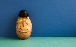 Senor Potato bowler hat serious face. Old fashioned style vegetable on blue wall green floor background. Copy space. Senor Potato bowler hat serious face. Old stock photography