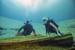 Senor & Teen - Cypress Tree Log. A senior and teen scuba diver hold onto the downed Cypress Tree log that extends across the opening to the Morrison Springs royalty free stock photography