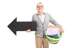 Senor tenant un panier de blanchisserie et une flèche Images libres de droits