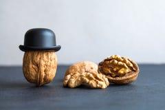 Senor walnut black hats, half nutshell on stone and gray background. Creative food design poster. Macro view selective. Senor walnuts black hats, half nutshell royalty free stock photos