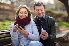 Senorman en vrouw met smartphones Stock Afbeelding