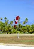 Sens du vent de mesure de vent de cône dans le petit aérodrome sur l'île tropicale avec des palmiers à une piste Photographie stock