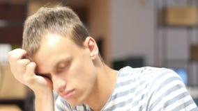 Sensación agotada Hombre joven frustrado que duerme en el trabajo en oficina metrajes