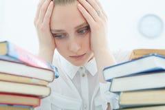 Sensación cansado Estudiante cansado femenino joven que trabaja en biblioteca Imágenes de archivo libres de regalías