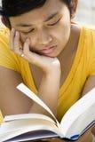 Sensación de la mujer joven triste mientras que lee Imagen de archivo libre de regalías