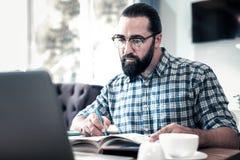 Sensación de ojos oscuros barbuda del hombre concentrada en el trabajo con el artículo foto de archivo