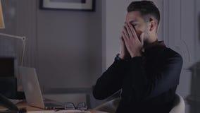 Sensación enfermo y cansado Hombre joven frustrado con los ojos rojos y los vidrios del dolor que se sientan en su lugar de traba almacen de video