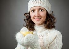 Sensación hermosa de la muchacha fría y tenencia a la taza de bebida caliente Foto de archivo