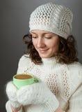 Sensación hermosa de la muchacha fría y tenencia a la taza de bebida caliente Foto de archivo libre de regalías