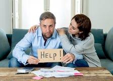 Sensación joven de los pares triste e hipoteca subrayada de las deudas de las cuentas que pagan que tiene problemas financieros imagen de archivo