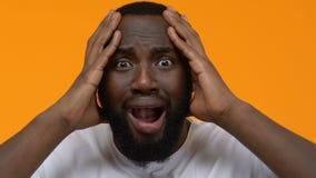Sensación masculina negra asustada nerviosa, noticias asombrosas, expresión del choque, tensión almacen de video