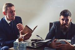 Sensaci?n relajado Inversi?n acertada en negocio Los hombres de negocios escriben informe financiero mientras que beben y fuman foto de archivo libre de regalías