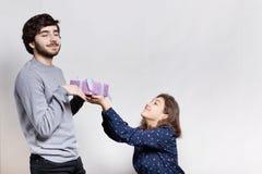 Sensaciones y concepto de las relaciones Una mujer joven sonriente que da un presente a su novio Un inconformista barbudo content Foto de archivo libre de regalías