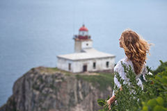 Sense of freedom. Blond-haired girl blown by the wind standing at the steep of rock before the sea and looking ahead in front of the lighthouse at the top of the Stock Images