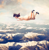 Sense of freedom. Beautiful woman flying over the mountains Royalty Free Stock Image