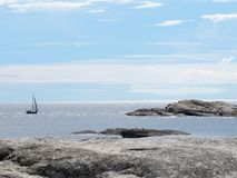 A sense of freedom. Beautiful sailboat sailing sail on the blue open sea spaces in Norway. Rocky shore in the foreground Royalty Free Stock Photo