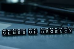 Sense of urgency text wooden blocks in laptop background. Business and technology concept stock photos
