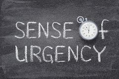 Sense of urgency watch. Sense of urgency phrase handwritten on chalkboard with vintage precise stopwatch used instead of O royalty free stock images