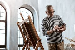 Sensibilità d'uso della camicia a strisce dell'artista occupata mentre dipingendo natura morta fotografia stock