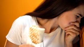 Sensibilità della ragazza malata, panino della tenuta, infezioni in alimento della via ed avvelenamento fotografie stock