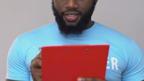 Sensibilità volontaria afroamericana in carte su fondo grigio, scrutinio sociale video d archivio