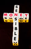 Sensible with money. Text ' sensible ' and 'money' in uppercase letters on small cubes arranged crossword style with common letter ' n ', dark background royalty free stock photo