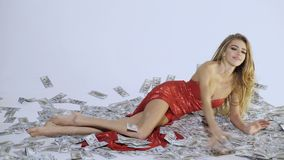 Sensitive blonde sexy woman in red dress. Beautiful young girl with long hair lying on banknotes.Hollywood style. Girl stock footage