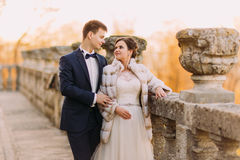 The sensitive eye contact bewtween happy newlywed couple standing near the old fence. Stock Image